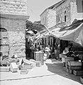 Bezoekers met tassen vol op een half-overdekte markt, op de voorgrond lege fruit, Bestanddeelnr 255-2470.jpg