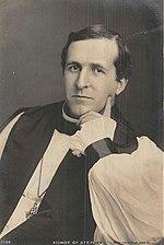 Zwart-witfoto van een donkerharige blanke man, zittend en met zijn linkerhand rond zijn kin, gekleed in bisschopsgewaden (rochet en chimere, borstkruis en administratief hemd)