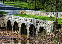 Stone bridge with five circular openings allowing a leaf-littered creek to pass through slowly