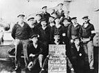 """Matrosen an Deck des Linienschiffs Prinzregent Luitpold mit einer Tafel: """"Soldatenrat Kriegsschiff Prinzregent Luitpold. Es lebe die sozialistische Republik"""""""