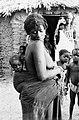 COLLECTIE TROPENMUSEUM Bella vrouw met kind in draagdoek op de rug andere kinderen en een vrouw kijken op de achtergrond toe TMnr 20010120.jpg