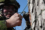 Canadian Army Cpl. Kody Lefort, with the 37th Combat Engineer Regiment, 37th Canadian Brigade Regiment, uses a parachute cord to secure C-4 to a tree trunk, during Exercise Southern Raider 13 at Fort Pickett 130304-A-HJ472-082.jpg