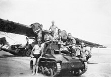 Soldiers sitting on a small armoured vehicle in front of a grounded aircraft