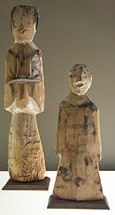 Photographie montrant deux figurines en bois représentant deux personnes. Celle de gauche est plus grande que l'autre.