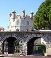 Vue d'une petite tour de château en fond avec au premier plan une muraille en pierre avec arcades barrées de fer forgé.