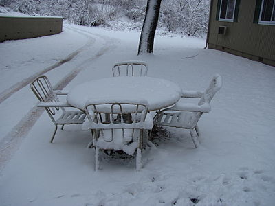 A image that describes what happens when chairs and other materials freezes and is covered with snow.