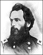 Black and white photo shows a bearded and dark-haired man in a dark uniform with two rows of buttons.