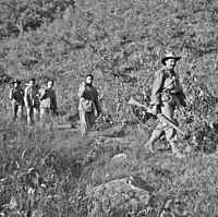 Three unarmed soldiers being led down a hill by two soldiers armed with rifles, one in the front the other in the rear.