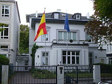 A two storey white building with an attic. Two flagpoles, one with the flag of Spain, the other with the European flag, are in front of the building.