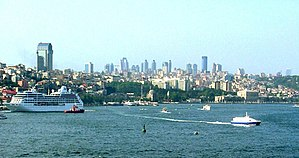 Bosphorus - A cruise ship (left) and Seabus (right) navigating through the Bosphorus, with the Dolmabahçe Palace seen at the right end of the frame.