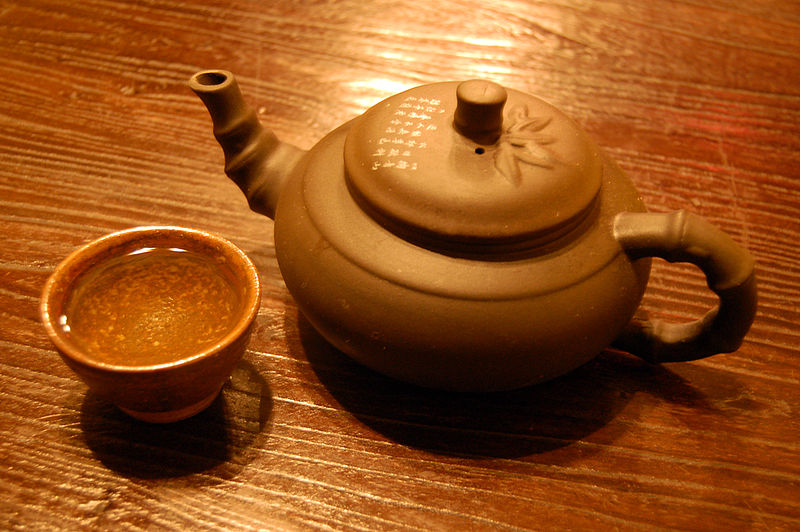 File:Cup of green tea and tea pot on table.jpg