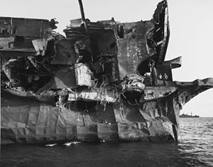 "USS Independence (CVL-22) - USS Independence ""Gilda"" test damage aft port quarter (note two sailors on the aft deck)"