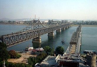 Sino-Korean Friendship Bridge - The bridge (on left side) viewed from Dandong, China. The Yalu River Broken Bridge is to its right.
