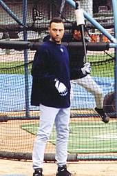 Derek Jeter stands in front of a batting cage wearing a navy long-sleeve shirt over a baseball uniform while holding a weighted bat in his left hand.