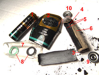 Zinc–carbon battery - Disassembled zinc chloride cell (similar to zinc carbon cell). 1:entire cell, 2:steel casing, 3:zinc negative electrode, 4:carbon rod, 5:positive electrode (Manganese dioxide mixed with carbon powder and electrolyte), 6:paper separator, 7:polyethylene leak proof isolation, 8:sealing rings, 9-negative terminal, 10-positive terminal (originally connected to carbon rod)