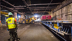 Workers constructing the station's upper concourse, which is located within part of the Grand Central Terminal's Madison Yard. There is construction equipment being stored alongside the walls of the yard.