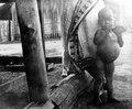 En liten pojke står vid sin moders ben. Madagaskar - SMVK - 010604b.tif