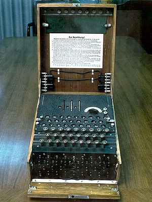 Enigma machine typewriter keypad over many rotors in a wood box