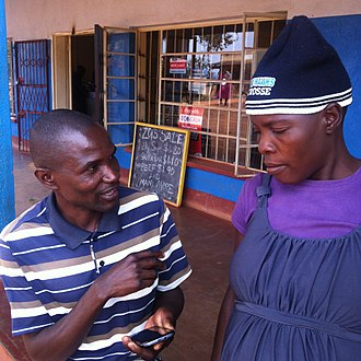 Census - Enumerator conducting a survey using a mobile phone-based questionnaire in rural Zimbabwe.