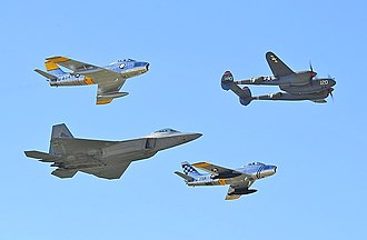Fighter aircraft - U.S. Air Force fighter aircraft representing different eras; a World War II P-38 Lightning (upper-right), a pair of F-86 Sabres from the early jet age and a modern F-22 Raptor (lower-left)