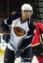 An African-Canadian hockey player. He wears a white jersey with dark blue shoulders with a stylized brown thrasher holding a hockey stick for a logo. He is standing with both hands on his stick with it on the ice.