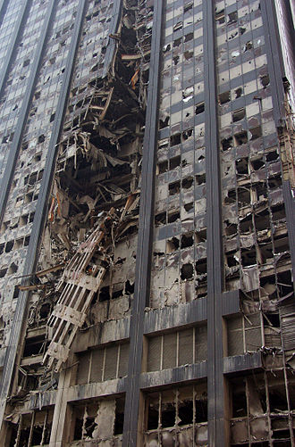 Deutsche Bank Building - Detail of gash in the facade imparted by the collapse of the World Trade Center. A segment of the South Tower facade is visible hanging from the gash.