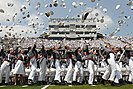 Cadets from the United States Military Academy at West Point toss their hats