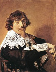 Man seated sideways on a chair, facing viewer, whose garment has an intricately patterned lace collar.