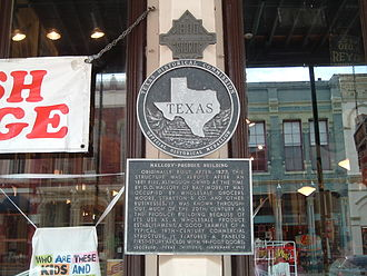 Strand Historic District - A historical marker on the Strand's old Mallory Produce building (now a curio shop), including a medallion above indicating the building survived the 1900 hurricane.