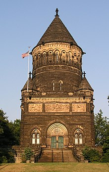 Victorian Gothic monument in brown stone. The first floor is square and the second is cylindrical with a conical roof.