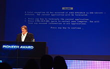 "Gabe Newell stands at a podium in front of a large screen. The screen is blue, similar to the ""blue screen of death"" for Windows, but with different text, including the word ""GLaDOS""."