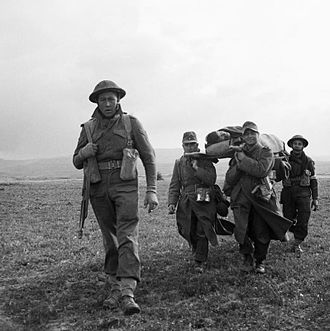 6th Armoured Division (United Kingdom) - German prisoners of war (POWs) carry a wounded British soldier during the 6th Armoured Division's attack on the town of Pichon in Tunisia, 8 April 1943.