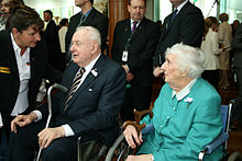 Whitlam, now in extreme old age, sits with an elderly lady as a woman bends to speak with him. He holds a metal cane. Other people, mostly men, stand behind him.