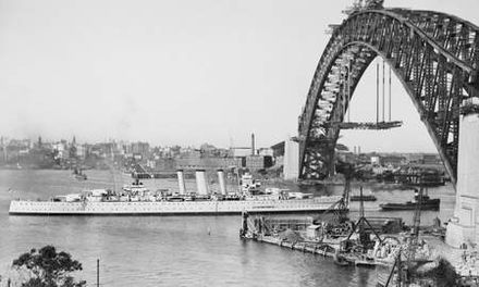HMAS Canberra sailing under the completed arch from which the deck is being suspended in 1930 HMAS Canberra sailing into Sydney Harbour in 1930.jpg