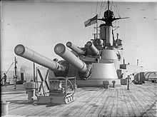 Two large gun turrets seen from the deck of a battleship; each turret has two long guns