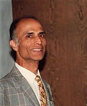 Photograph of a bald man wearing suit and tie.
