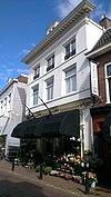 foto van Hoekpand van momenteel drie bouwlagen, met zadeldak loodrecht op de straat en wolfseind voor, voorgevel met kroonlijst