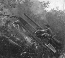 A tracked vehicle fitted with a large gun negotiates its way up a steep hillside (about 45˚, or one-in-one). The crew of two in the open cab are leaning forward and holding on tightly to avoid falling out backwards.