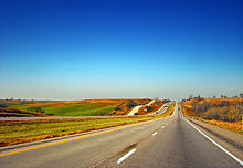 A highway underneath a clear sky surrounded by harvested cropland and green pastures.
