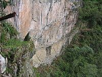 Photographie.Un pont-mur en pierres avec trouée pour le passage d'un torrent. Des poutres assurent la continuité du passage vers un escalier à flanc de montagne