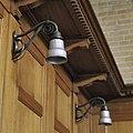 Interieur, overzicht van twee wandlampen, ontwerp van W.H. Gispen, hangen aan de achterwand van een herenbank, in de kerk - Rotterdam - 20387282 - RCE.jpg