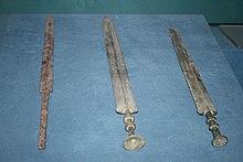 Photographie de deux épées en bronze et d'une épée en fer de tailles similaires. Celle de gauche se distingue des deux autres par la forme de sa lame et de son manche.