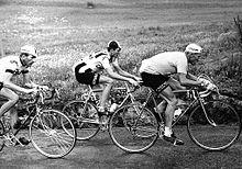 Photographie en noir et blanc montrant trois cyclistes lors d'une course.