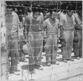 Japanese Prisoners of War at Guam, with bowed heads after hearing Emperor Hirohito make announcement of Japan's... - NARA - 520991.tif