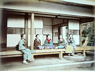 Engawa - Veranda-like engawa with people for scale. Note the slope of the ground under the engawa, and the traditional stone step.