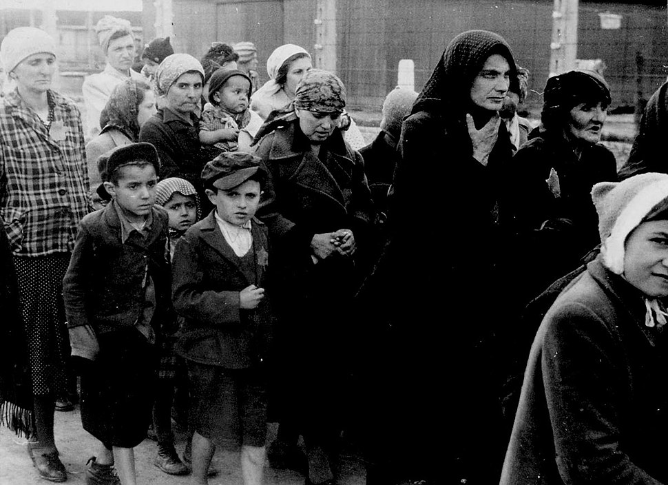 Jewish women and children from Subcarpathian Rus who have been selected for death at Auschwitz-Birkenau walk toward the gas chambers