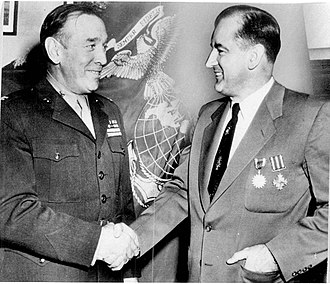Joseph McCarthy - McCarthy receiving his DFC and Air Medal from Colonel John R. Lanigan, commanding officer of Fifth Marine Reserve District, December 1952.