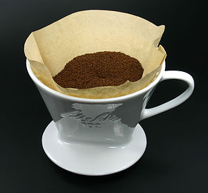 Melitta - A Melitta coffee filter, containing ground coffee, in a single cup brewing holder