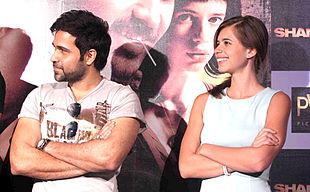 Koechlin sitting beside Emran Hashmi looking away from the camera
