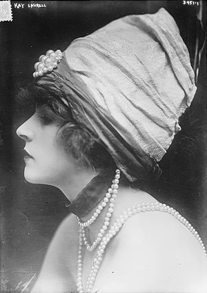 Peach basket hat - Kay Laurell in an unusual high-crowned and fabric draped variation on the peach basket, c. 1910